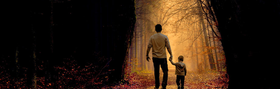 Man and child walking in the woods